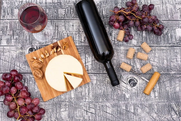 Odgórnego widoku czerwone wino z winogronem i serem na pokładzie i na biały drewniany horyzontalnym