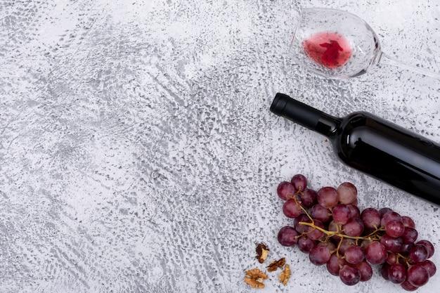Odgórnego widoku czerwone wino z winogronem z kopii przestrzenią na lewicie na bielu kamieniu horyzontalnym