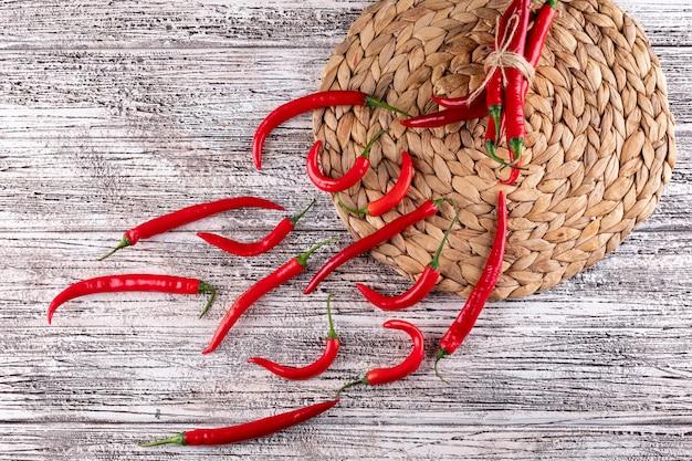 Odgórnego widoku czerwonego chili pieprz na beżowej słomy talerza macie na biały drewniany horyzontalnym