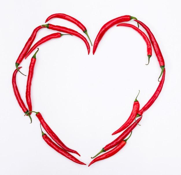 Odgórnego widoku czerwonego chili pieprzu serce na biały horyzontalnym