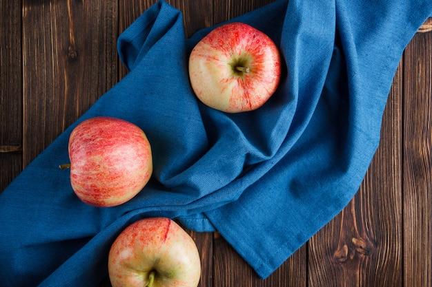 Odgórnego widoku czerwoni jabłka na błękitnym płótnie i drewnianym tle. poziomy