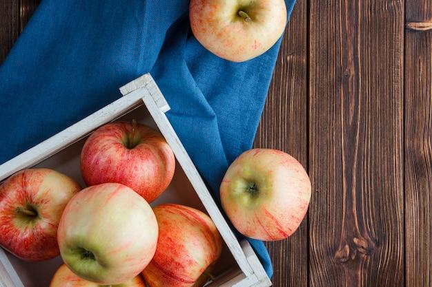 Odgórnego widoku czerwoni jabłka w drewnianym pudełku i wokoło na błękitnym płótnie i drewnianym tle. poziomy