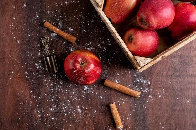 Odgórnego widoku czerwoni jabłka w skrzynce z cynamonem na brown drewniany horyzontalnym