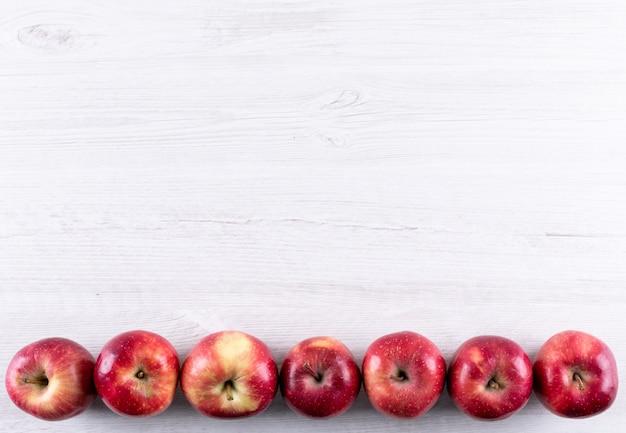 Odgórnego widoku czerwoni jabłka z kopii przestrzenią na biały drewniany horyzontalnym