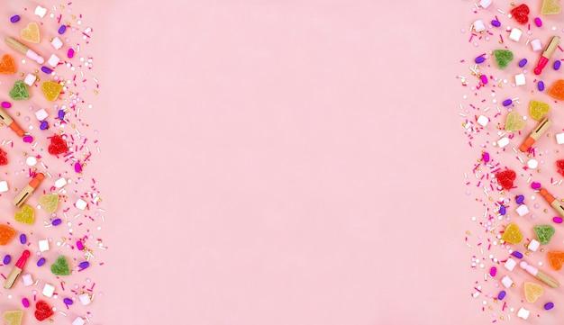 Odgórnego widoku dekoraci asortowani gumowaci cukierki i galaretowych cukierków szczęśliwy wakacyjny pojęcie. mieszkanie leżało kolorowe cukierki na pięknym różowym biurku. skopiuj miejsce