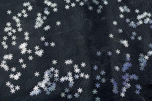 Odgórnego widoku dekoracyjni płatki śniegu na czarnym tle