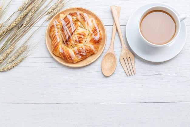 Odgórnego widoku duńscy ciasta na białym drewnianym stołowym tle