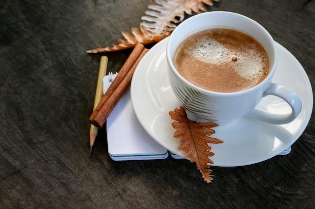 Odgórnego widoku filiżanka kawy z suchym liściem na drewnianym, copyspace.