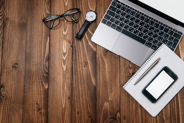 Odgórnego widoku fotografia drewniany biurowy biurko z laptopem, eyeglasses, zegarka, telefonu i notatnika tłem ,.