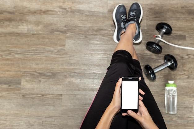 Odgórnego widoku fotografia żeńska sprawność fizyczna z telefonem. pojęcie sportu.
