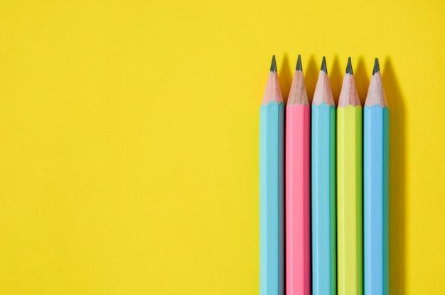 Odgórnego widoku grupa drewniani pastelowego koloru ołówki na kolorze żółtym tapetuje tło