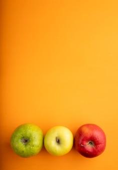 Odgórnego widoku jabłczanej mieszanki czerwoni żółci i zieleni jabłka na dnie z kopii przestrzenią na pomarańczowym tle
