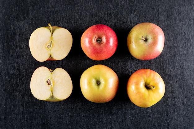Odgórnego widoku jabłka pokrajać na czarny drewniany horyzontalnym