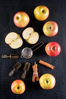 Odgórnego widoku jabłka z cynamonem i herbatą ustawiają na czarnym drewnianym vertical