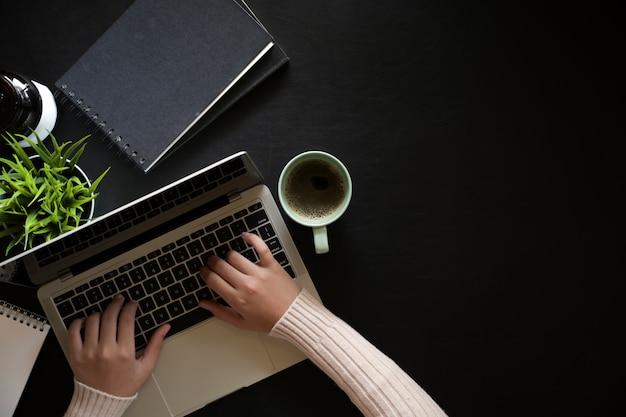 Odgórnego widoku kobieta używa laptop na ciemnym rzemiennym workspace biurku