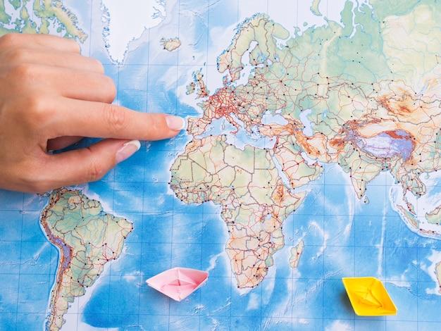 Odgórnego widoku kobiety ręka wskazuje na miejscu na mapie
