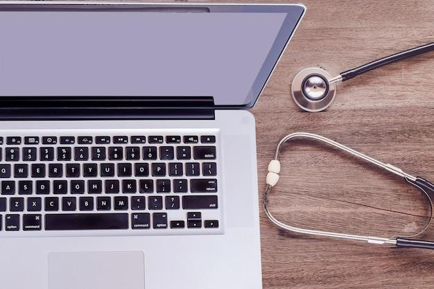 Odgórnego widoku laptop z stetoskopem na starym drewno stole.