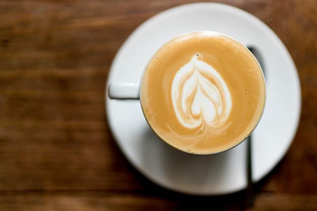 Odgórnego widoku latte sztuki kawa na drewnianym. piankowa latte art w kształcie serca. s.