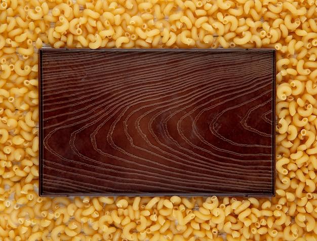 Odgórnego widoku łokcia makaronowy makaron z kopii przestrzenią na białym drewnianym tle