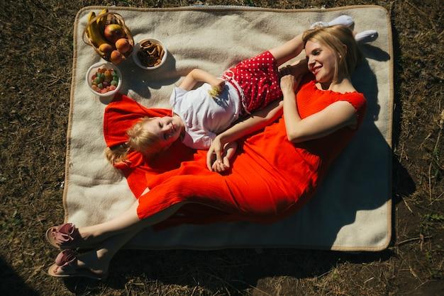 Odgórnego widoku matka i córka kłaść na koc