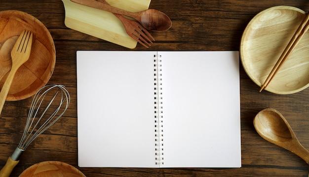 Odgórnego widoku notatnik pisać przepisie menu i drewniani kuchenni naczynia gotuje narzędzia na drewno stołu tle.