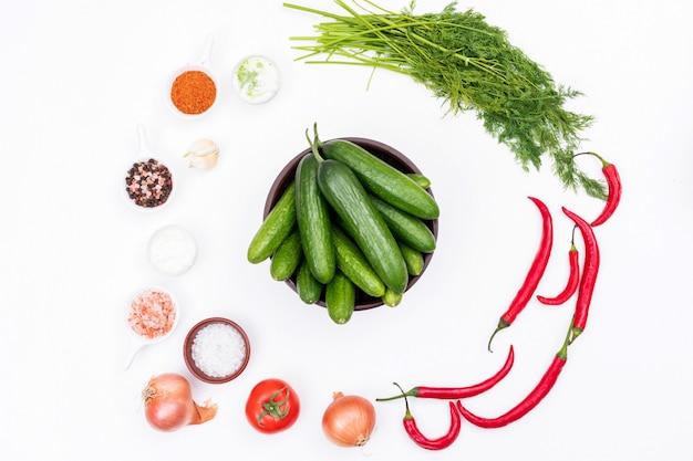 Odgórnego widoku ogórek w pucharze z czosnku chili koperem i pikantność na biały horyzontalnym