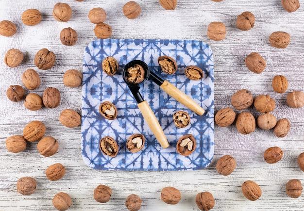 Odgórnego widoku orzechy włoscy i dziadek do orzechów w talerzu na drewniany horyzontalnym