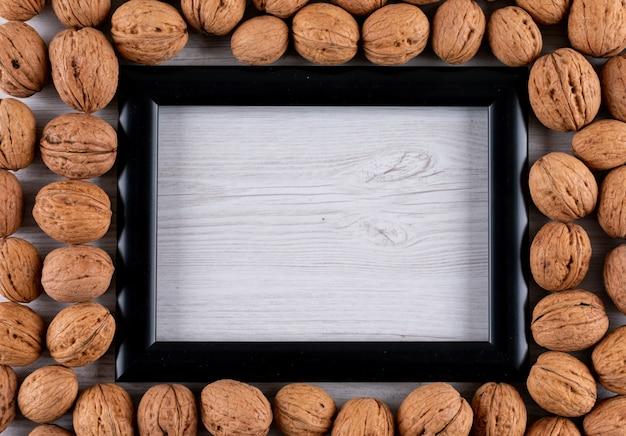 Odgórnego widoku orzechy włoscy z kopii przestrzenią w czerni ramie w mętnieniu na biały drewniany horyzontalnym
