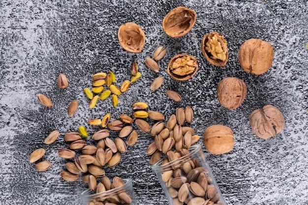 Odgórnego widoku pistacje i orzech włoski w szkle na popielatej teksturze horyzontalnej