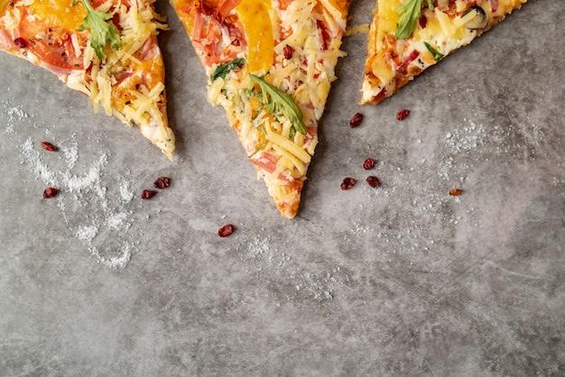Odgórnego widoku pizzy plasterki z cementowym tłem
