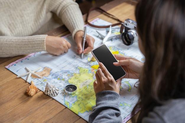 Odgórnego widoku podróżnicy planuje w wakacjach dla urlopowej wycieczki z mapą, podróży pojęcie