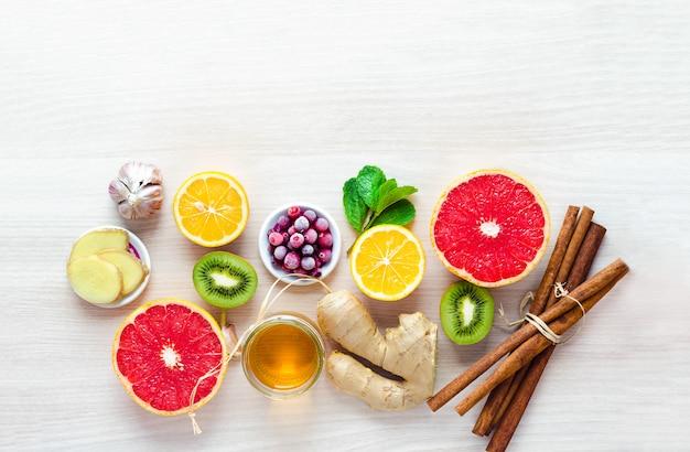 Odgórnego widoku połówki cytrus owoc i produkty z witaminą c na lekkim drewnianym tle z kopii przestrzenią