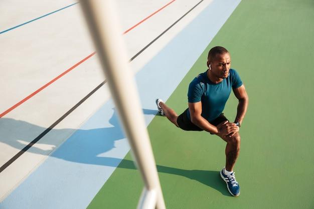 Odgórnego widoku portret młody afrykański sportowiec robi rozciąganiu