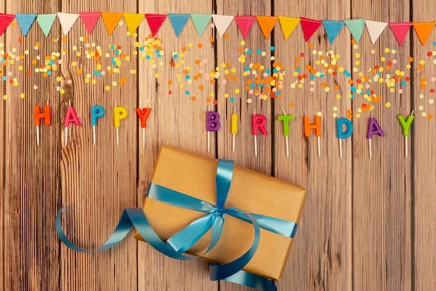 Odgórnego widoku prezent urodzinowy na drewnianym tle
