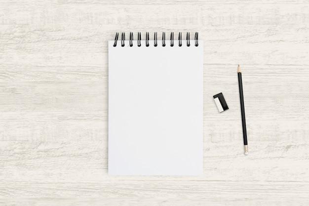 Odgórnego widoku przedmiota tło pusty notatnik i ołówek na drewnianej teksturze.