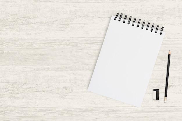 Odgórnego widoku przedmiota tło pusty notatnik i ołówek na drewnie.