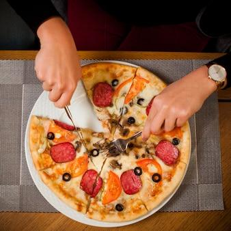 Odgórnego widoku przyrodnia kiełbasiana pizza z człowiekiem, rozwidlenie i nóż w bielu talerzu