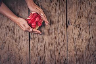 Odgórnego widoku ręki mienia prezenta pudełko na drewnianym tle