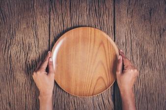 Odgórnego widoku ręki mienia talerz na drewnianym tle
