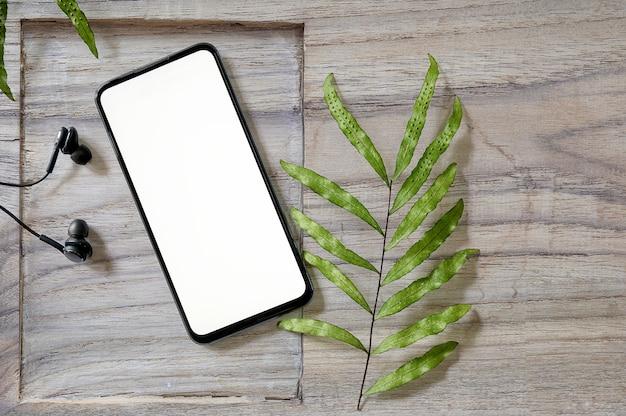 Odgórnego widoku smartphone z pustym ekranem i słuchawką na drewnianym tle.