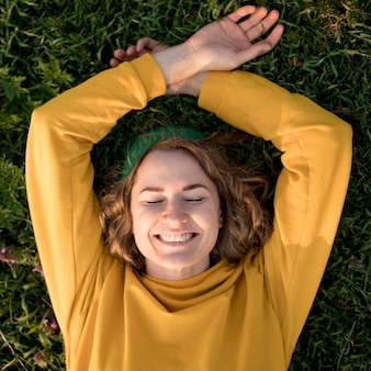 Odgórnego widoku smiley dziewczyna zostaje na trawie