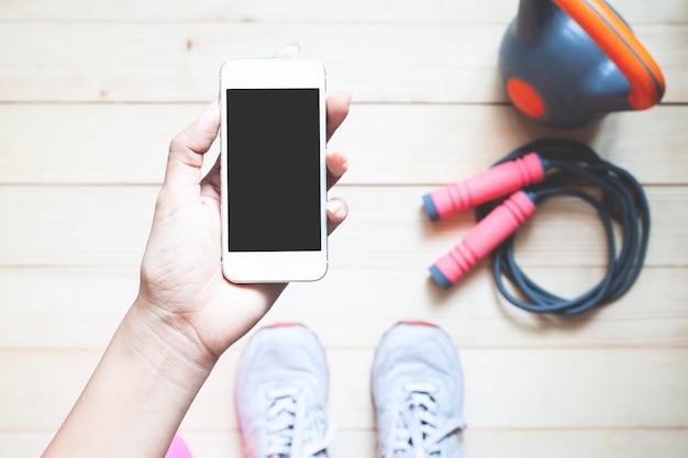 Odgórnego widoku sporty kobieta trzyma mądrze telefon. mockup aplikacji mobilnej.