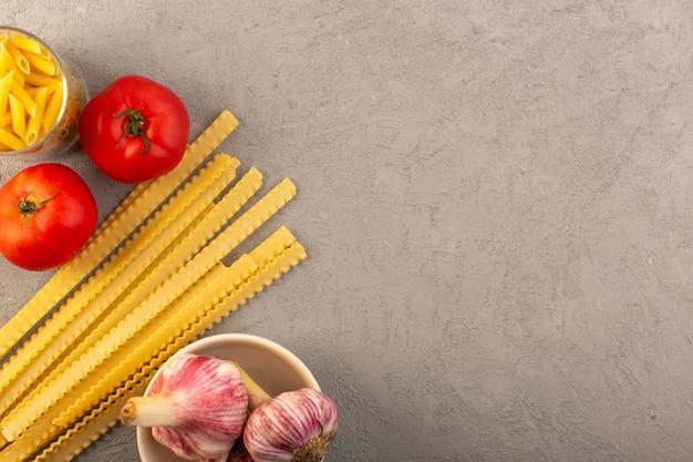 Odgórnego widoku surowego makaronu koloru żółtego suchy długi włoski makaron wraz z czerwonymi pomidorami i czosnkiem odizolowywającymi na szarym tła warzyw jedzenia posiłku