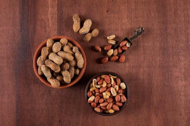 Odgórnego widoku surowi arachidy w pucharze na drewniany brown horyzontalnym
