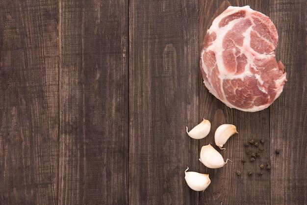 Odgórnego widoku surowy świeży mięso i czosnek, pieprz na drewnianym tle