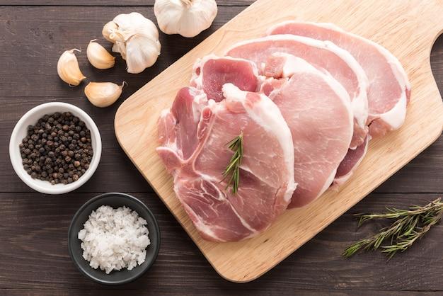 Odgórnego widoku surowy świeży mięso i sól, pieprz, czosnek na drewnianym tle
