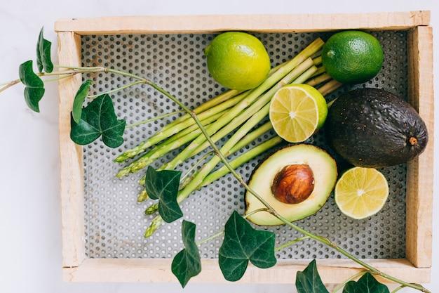 Odgórnego widoku świezi zieleni zdrowi warzywa w drewnianym pudełku i bluszcz roślinie na białym marmurze