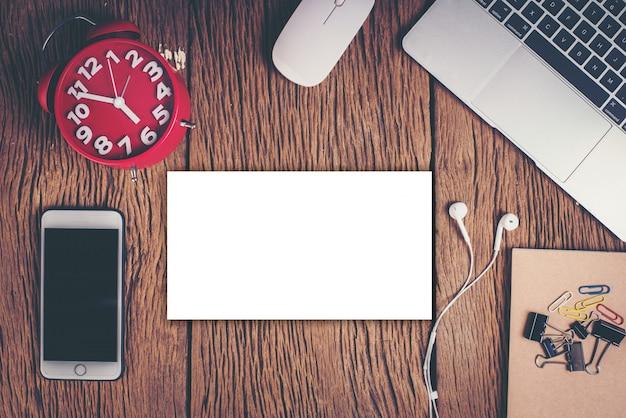 Odgórnego widoku telefon i workspace na drewnianym tle
