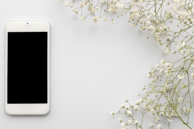 Odgórnego widoku telefon komórkowy z pustym ekranem z kwiatami na białym tle. leżał płasko kwiatowy rama z miejsca kopiowania.
