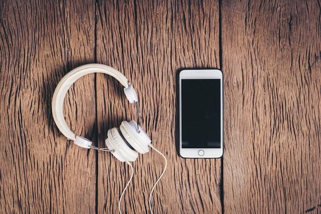 Odgórnego widoku telefonu i hełmofonu drewniany tło